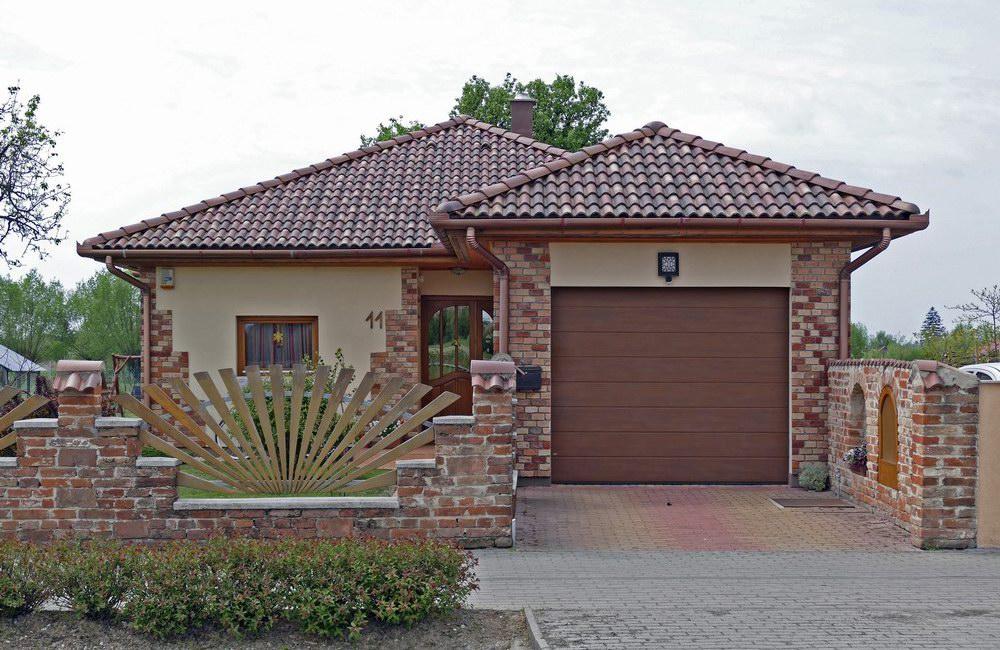 Családi ház és a nyílászárókhoz harmonikusan illeszkedő garázskapu